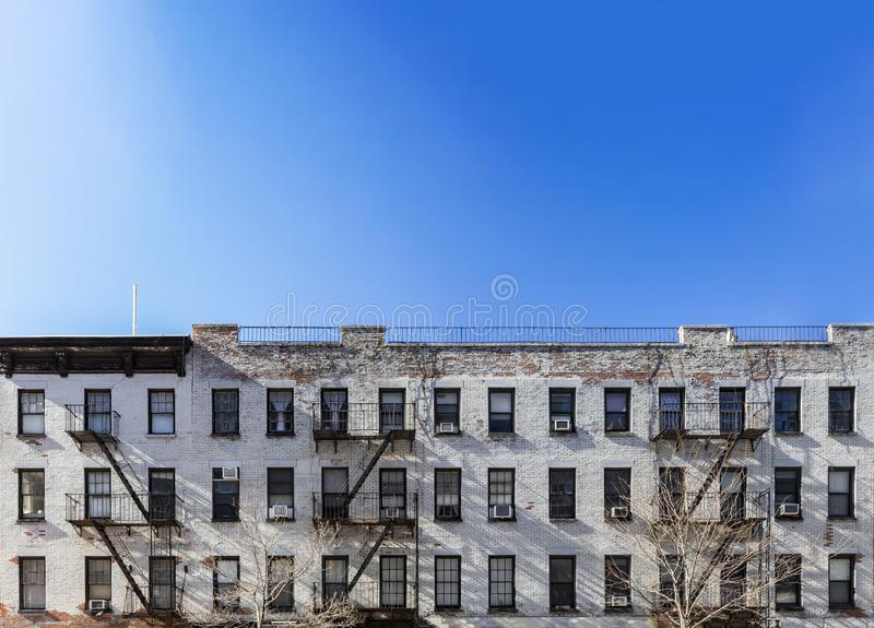 Old white brick apartment building with windows and fire escapes and an empty blue sky background overhead in New York City stock photo