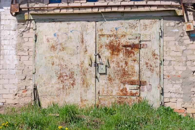 Old white brick garage with rusty gate stock photos