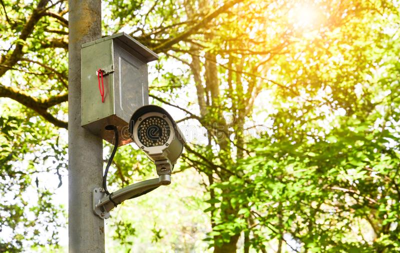 Old white cctv camera or surveillance on the pole for monitoring in public park royalty free stock photography