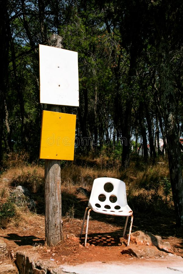 Old white chair and wooden pole with sign boards royalty free stock image