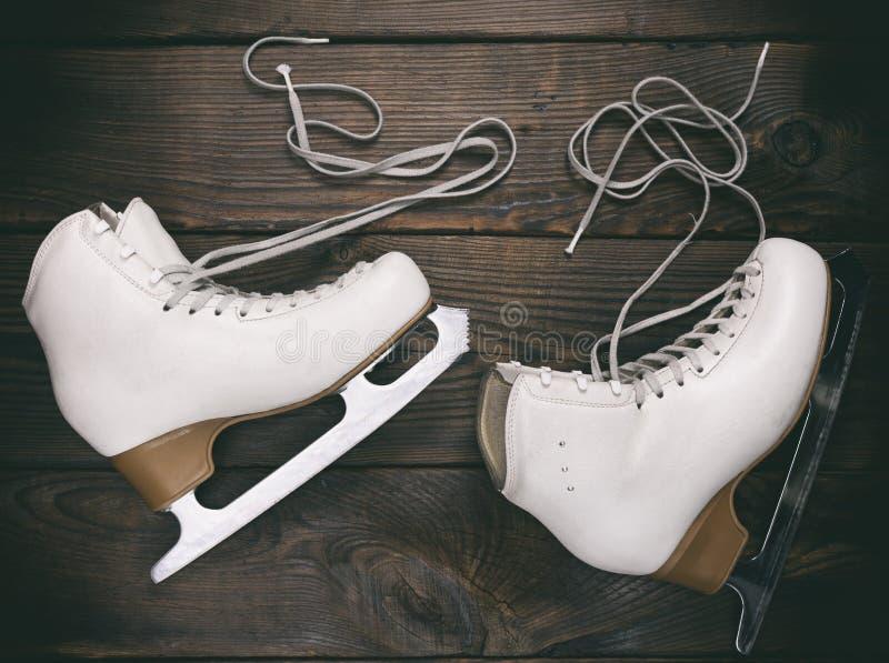 Old white female skates for figure skating with unbound laces. A pair of old white female skates for figure skating with unbound laces lie on a brown wooden stock photo