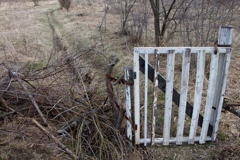 An old white gate closes the entrance along a dirt country road, two tracks in the field stock images