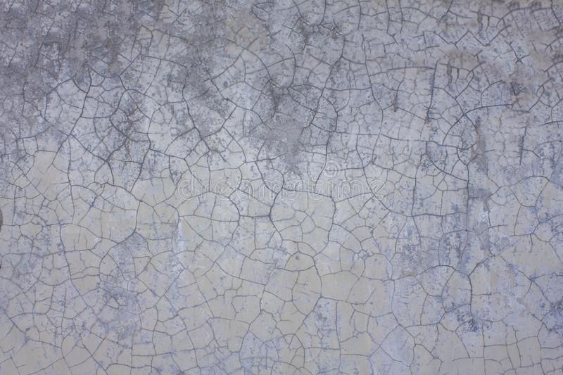 A old white gray purple wall with cracks and stains of dirt. rough surface texture. Old white gray purple wall with cracks and stains of dirt. rough surface royalty free stock images