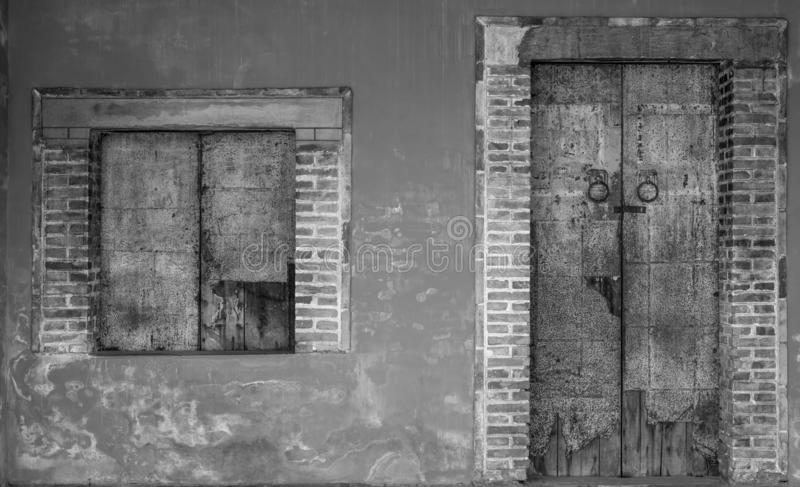 Old white and grey brick wall of ancient building. Concrete and brick building with closed wooden door and window. Exterior of old stock images