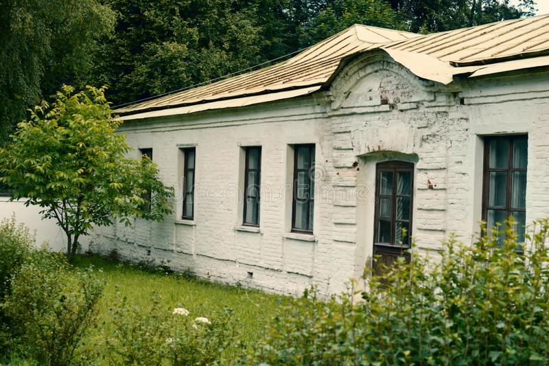 The old white one-storey historical building. From a white brick in the forest park with greens and trees stock images