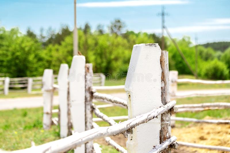 Old white painted zigzag wooden fence at ranch or horse farm with green forest and blue sky on background. Rural. Countryside landscape stock photos