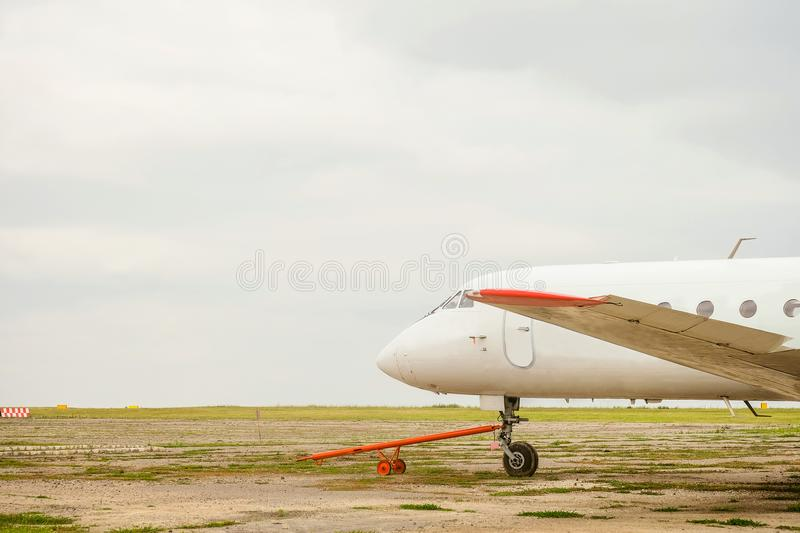 Old white passenger plane with a cruel hitch for transportation. Standing in the parking lot stock photography