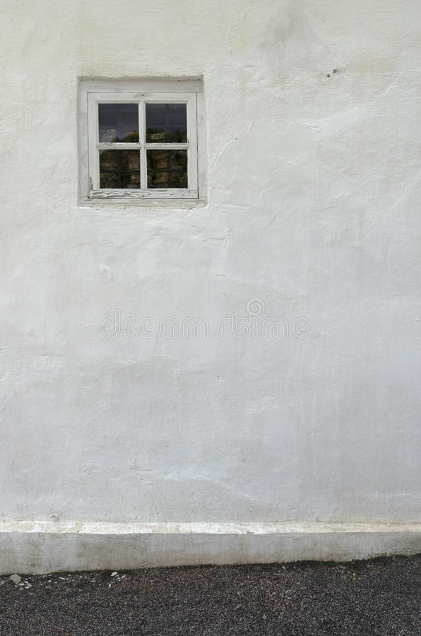 The old white plastered wall with a small window and a gravel pa stock image