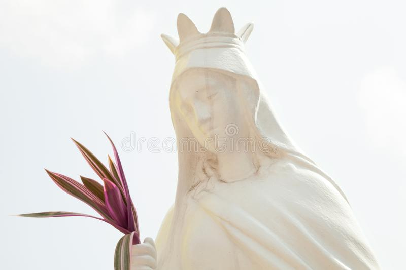 Old white sculpture of a saint woman wearing a crown and holding a bouquet. Catholic holy vintage statue against the light sky stock photos