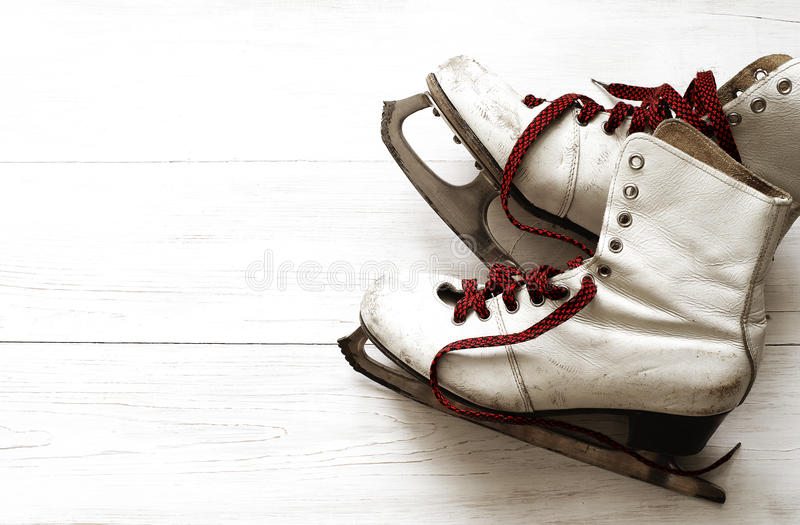 Old white skates for figure skating. On a wooden surface stock photos