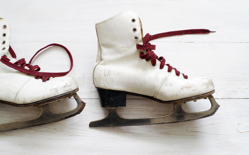 Old white skates for figure skating. On a wooden surface stock image