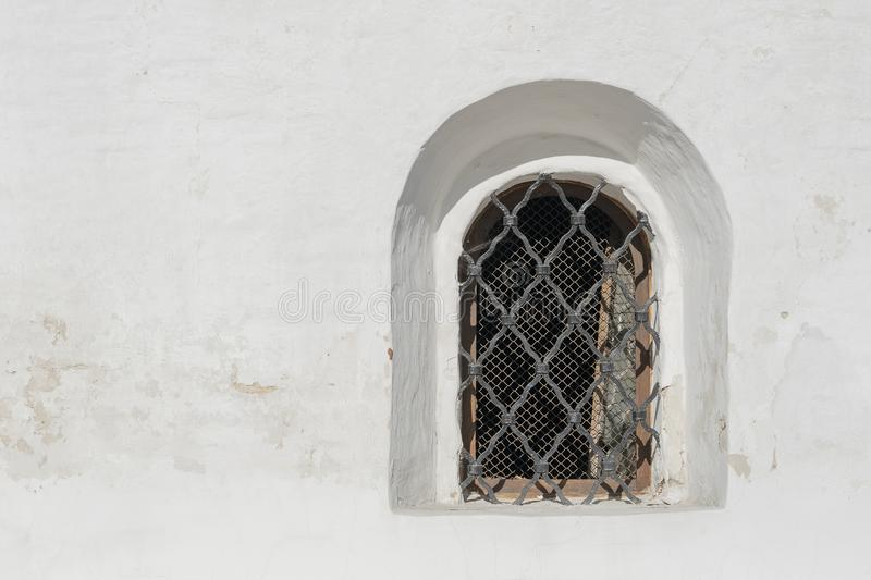 Old white stone wall with one grating window royalty free stock image
