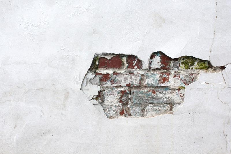 Old white wall in cracks with red brick. Urban texture. Old red brick wall with damaged white plaster. Plastered brick wall, rough royalty free stock images