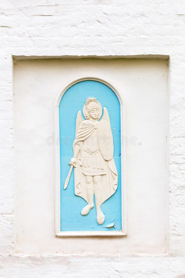 On an old white wall the relief of an angel. Guardian angel is depicted on the wall of brick painted white stock images