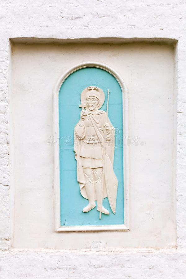 On an old white wall the relief of an angel. Guardian angel is depicted on the wall of brick painted white stock photography