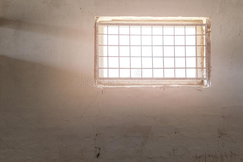 Old white wall with window covered by iron grate. Sun shining through grill. Mental prison . Enlightment concep. T. Copyspace stock photography