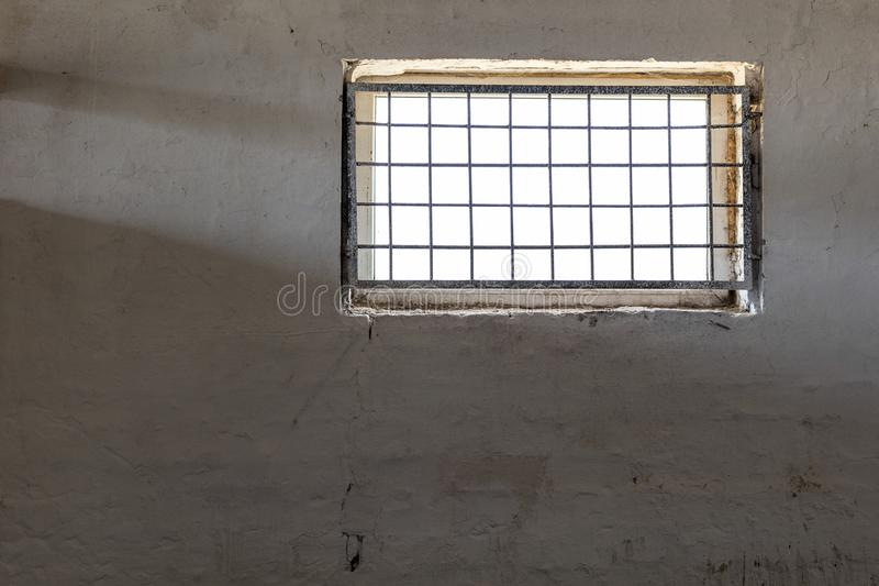 Old white wall with window covered by iron grate. Sun shining through grill. Prison room interior . Enlightment concept. Copyspac. E royalty free stock photography