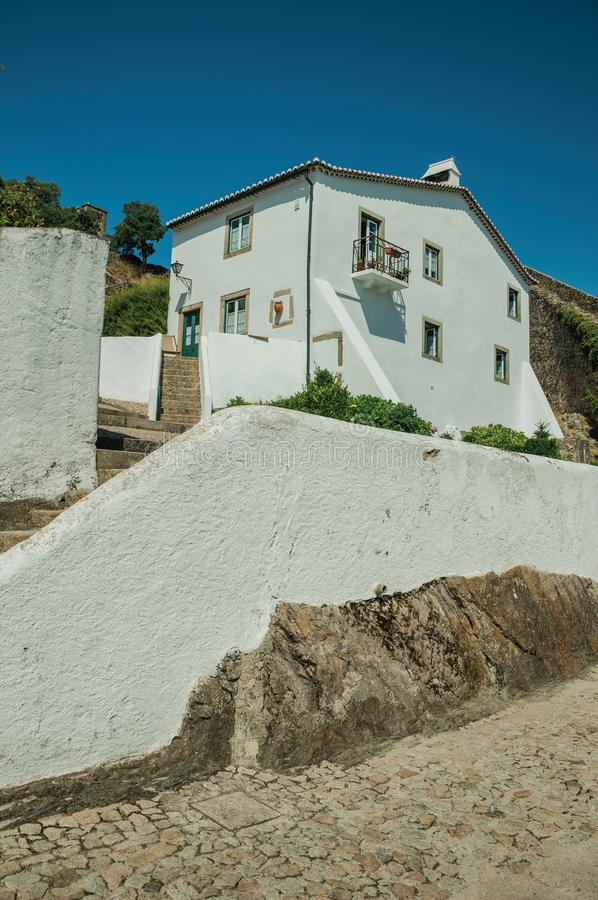 Old whitewashed wall house over rocks with stairs and plants royalty free stock images