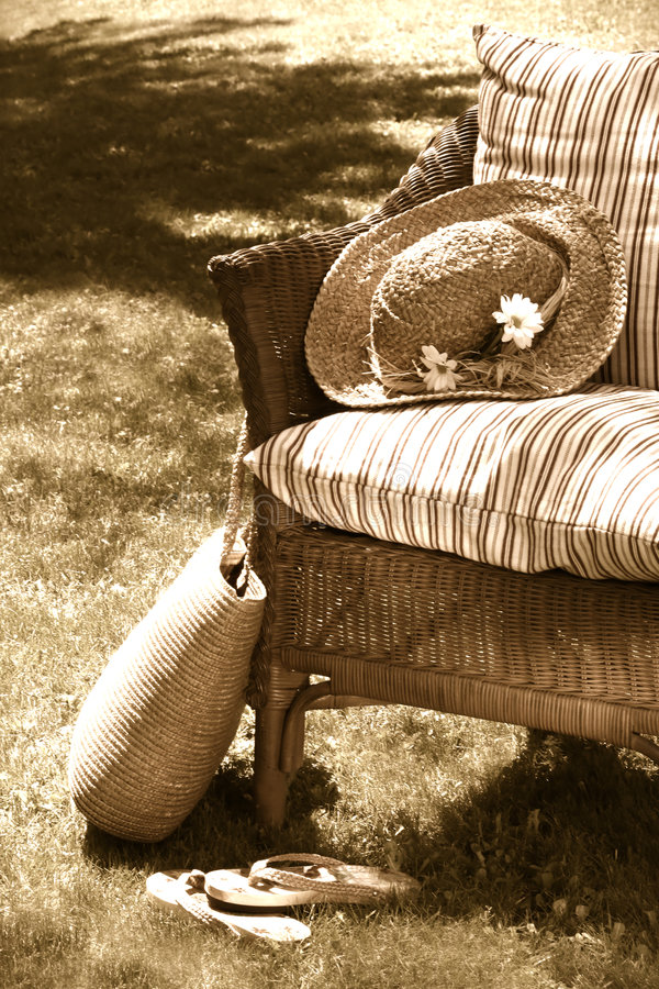 Old wicker chair. Grass lawn with a wicker chair waiting for someone to relax on a hot summer's day royalty free stock image