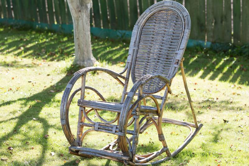 Old wicker rocking chair in the garden. On the grass stock image