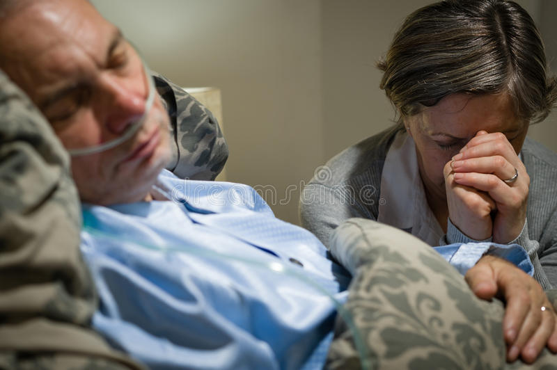 Download Old Wife Praying For Terminally Ill Husband Stock Photo - Image: 30862130