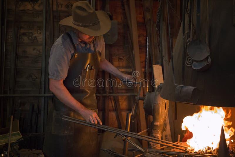 Old Wild West Blacksmith. Blacksmith working with iron in an old wild west blacksmith shop stock photos