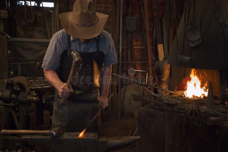 Old Wild West Blacksmith Hammering. Blacksmith working with iron in an old wild west blacksmith shop royalty free stock image