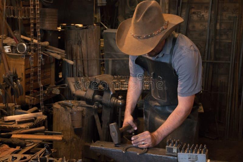 Old Wild West Blacksmith Hammering. Blacksmith working with iron in an old wild west blacksmith shop stock photos