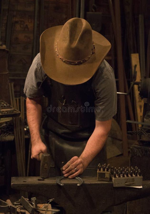 Old Wild West Blacksmith. Blacksmith working with iron in an old wild west blacksmith shop stock image