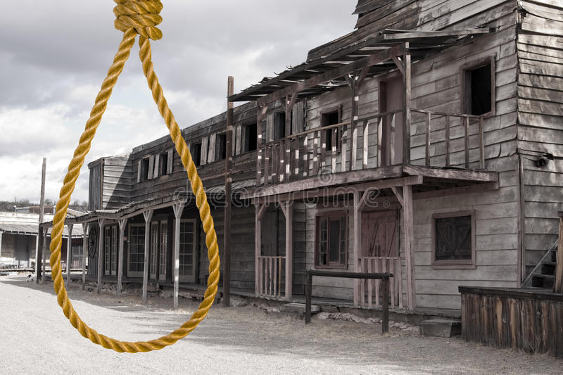 Old Wild West Cowboy Town Justice. A hangman's noose hangs in the deserted street of an old wild West town royalty free stock images