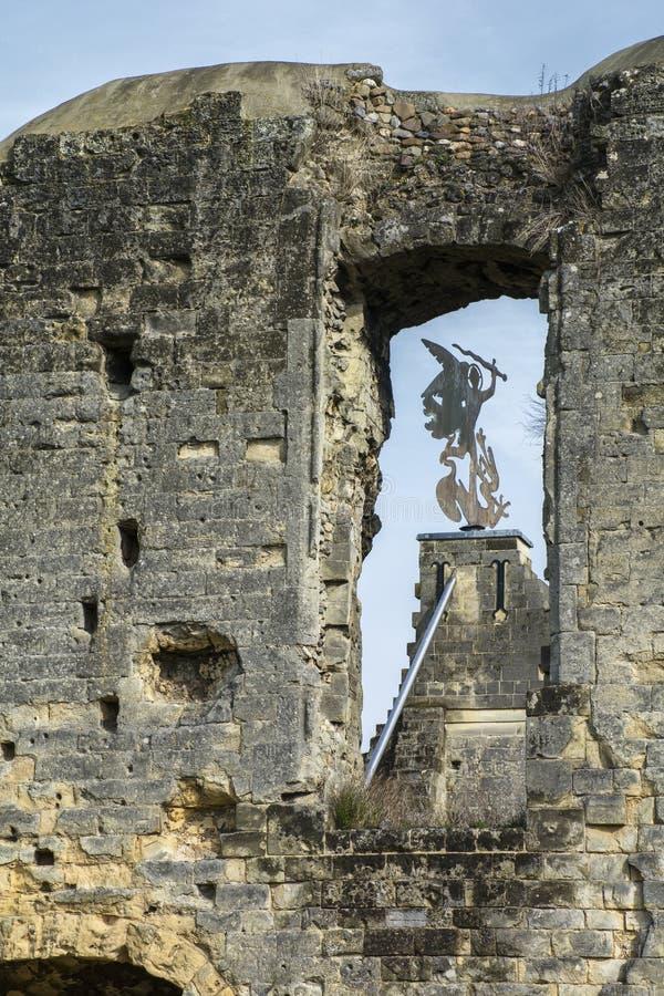 Old wind vane in aperture of ancient european ruins under the blue sky. Old black wind vane in aperture of ancient european ruins under the blue sky royalty free stock photos