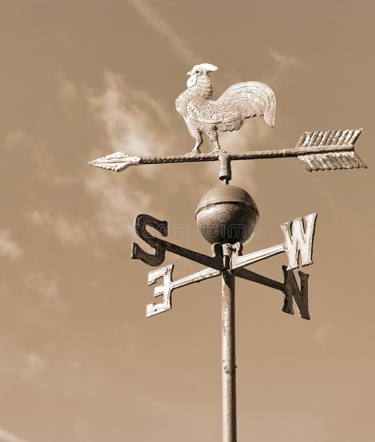 old wind vane with cock in iron in sepia toned royalty free stock images
