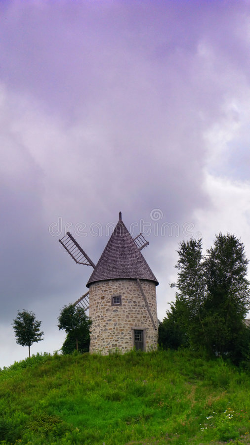 Old windmill. An old stone windmill with wooden blades on a grassy hill with stormy sky in the background royalty free stock images
