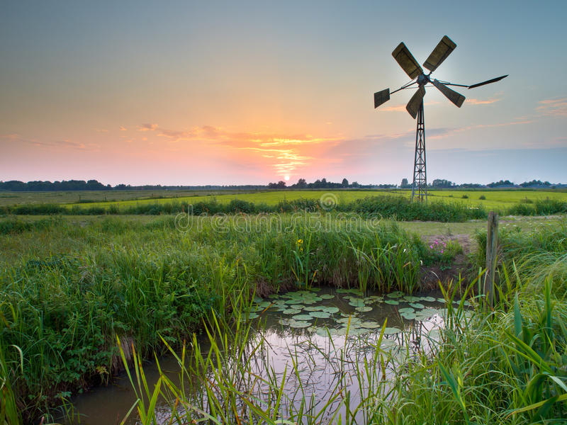 Old windmill in agricultural area in the Netherlands. Old american windmill during sunset in dutch rural setting stock photography