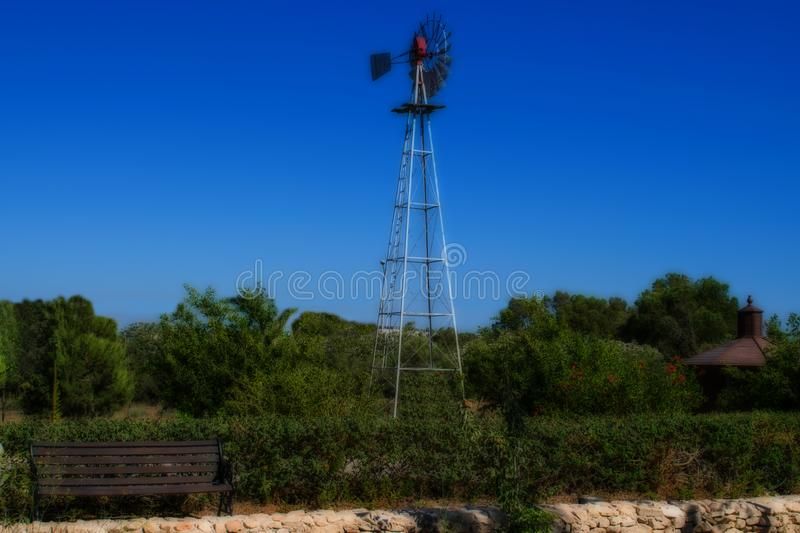 Old Windmill in the Field. An old windmill in a field as an alternative energy solution royalty free stock photography