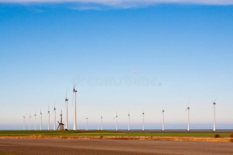 Old windmill and new windmills stock photo