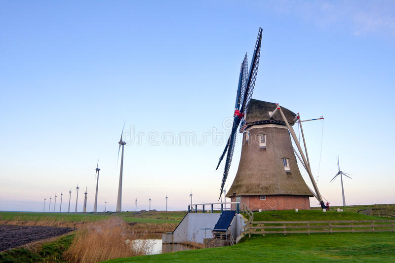 Old windmill and new windmills royalty free stock photography