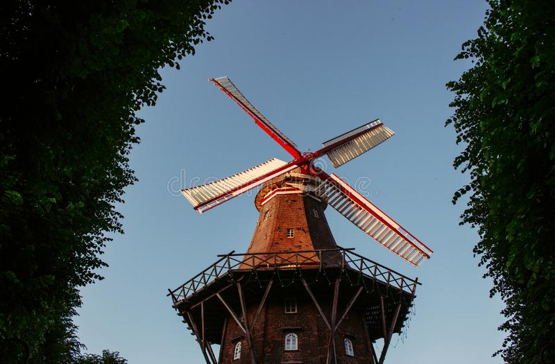 Old windmill in summer park. Windmill in city garden in the morning light. Historic architecture in Europe. Rural holland landmark. Mill with trees. Wind stock photo