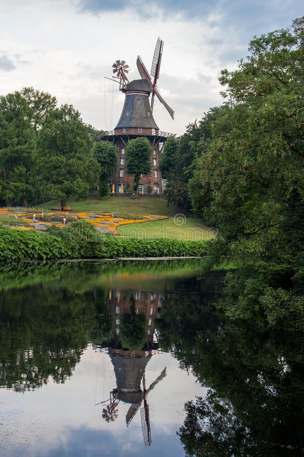 Old windmill in summer park with pond. Windmill with reflection in water in city garden. Bremen, Germany - 15/06/2019: old windmill in summer park with pond stock image