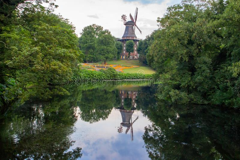 Old windmill in summer park with pond. Windmill with reflection in water in city garden. stock photography