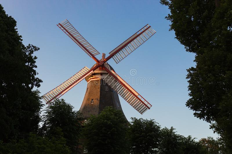 Old windmill in summer park. Windmill in city garden in the morning light. Historic architecture in Europe. Rural holland landmark. Mill with trees. Wind royalty free stock photography