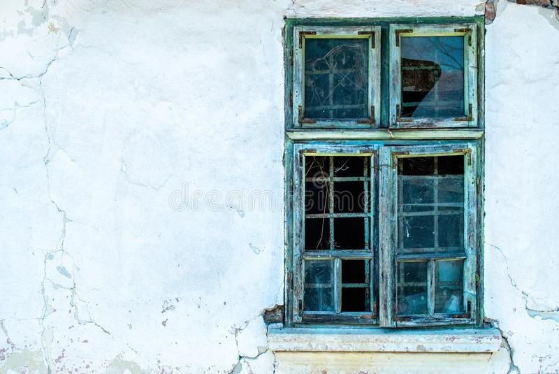 Old window in broad daylight on a crumbling wall of the old house stock images
