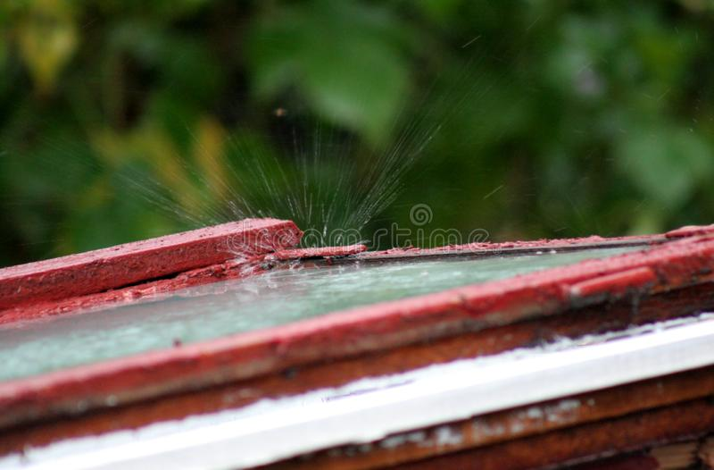 An old window frame with glass. On which rain falls. Rainy drops that hit the glass are broken, creating the effect of breaking glass. This phenomenon is often stock images