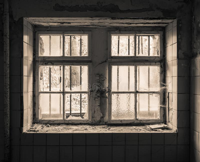 Old window with grid. An old dilapidated window with a grid stock images