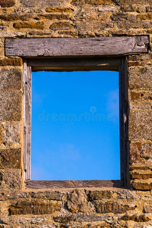 Old Window onto a Blue Sky. Window frame in an old stone wall onto a blue sky. No glass and a wooden frame and lintel royalty free stock image