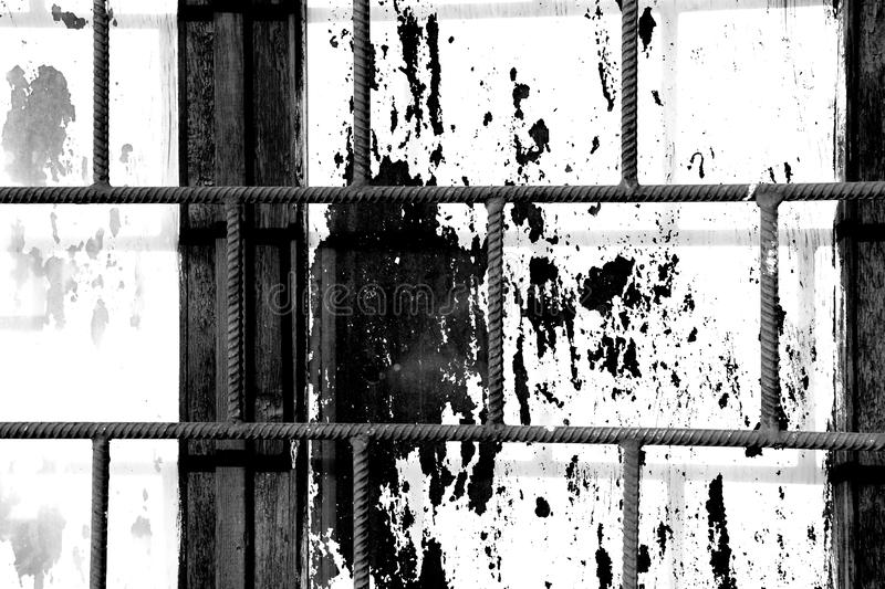 Old window painted white paint behind a rusty bars, black and white. Old window painted white paint behind a rusty bars closeup, black and white stock photo