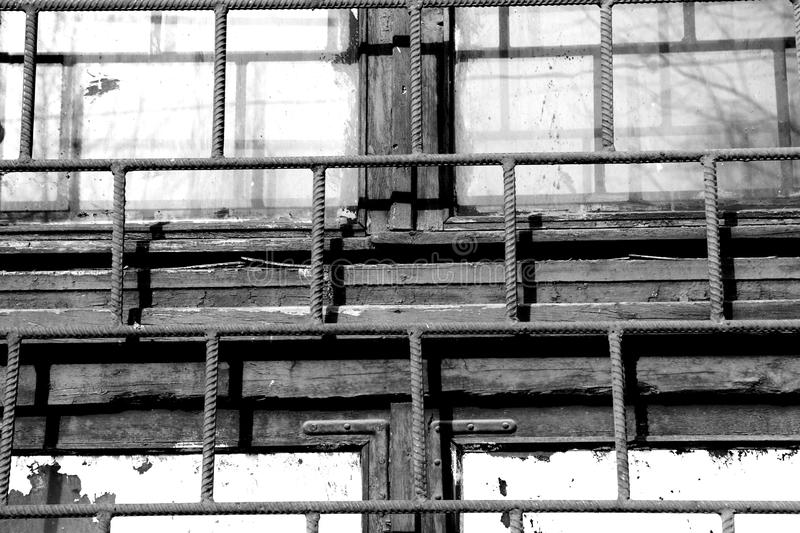 Old window painted white paint behind a rusty bars, black and white. Old window painted white paint behind a rusty bars closeup, black and white royalty free stock photography