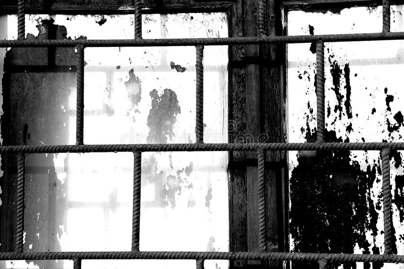 Old window painted white paint behind a rusty bars, black and white. Old window painted white paint behind a rusty bars closeup, black and white royalty free stock photos