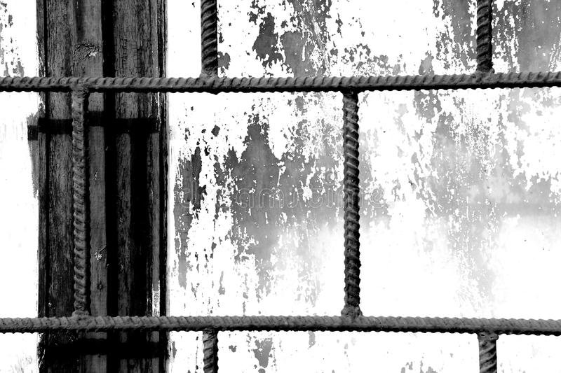 Old window painted white paint behind a rusty bars, black and white. Old window painted white paint behind a rusty bars closeup, black and white stock photography