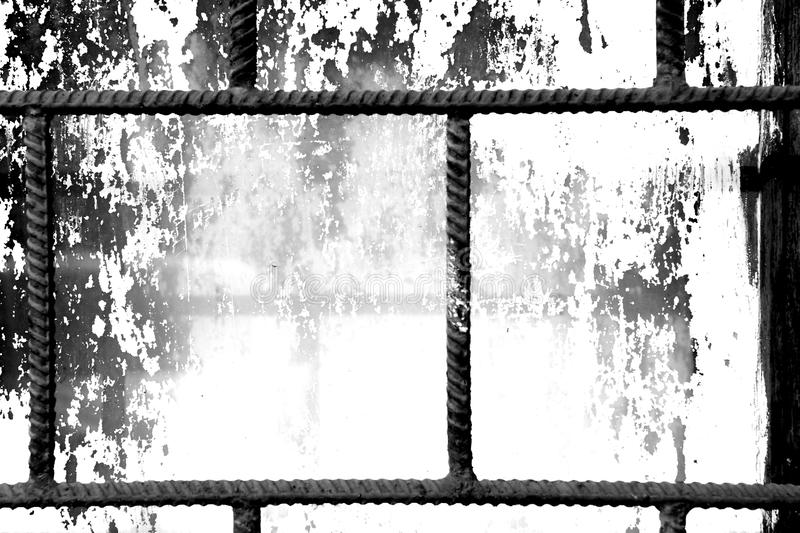 Old window painted white paint behind a rusty bars, black and white. Old window painted white paint behind a rusty bars closeup, black and white stock photos